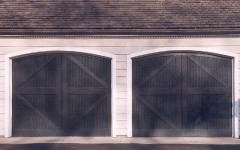 Dual arched black overhead doors without windows